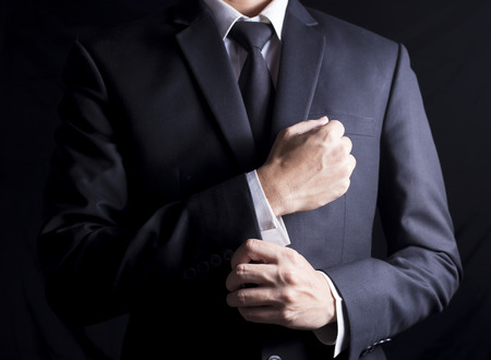 luxury lifestyle: Businessman Fixing Cufflinks his Suit Stock Photo