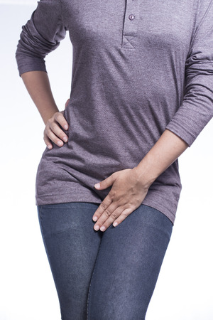urination: Woman with Hands Holding Her Crotch