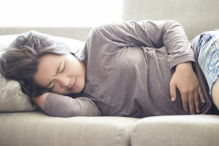 Woman Suffering from Stomachache on Sofa Imagens - 50927516