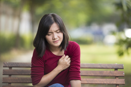 Woman Has Chest Pain Sitting on Bench at Park Imagens - 50955604