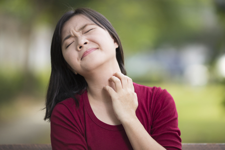Woman Scratching Her Neck Sitting on Bench at Park 스톡 콘텐츠