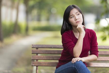 pretty teenage girl: Sad Woman Sitting on Bench at Park Stock Photo