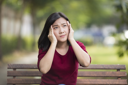 complications: Woman Has Head Ache Sitting on Bench at Park