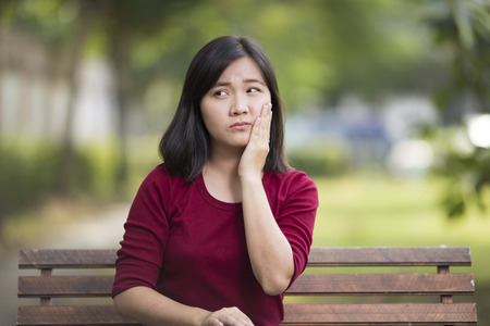 tooth ache: Woman Has Tooth Ache Sitting on Bench at Park