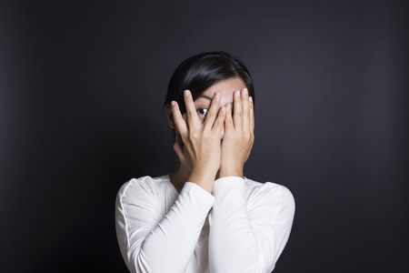 timid: Woman hiding face laughing timid Stock Photo