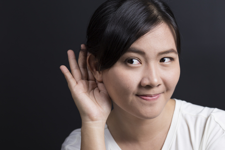 listens: Woman with hand behind her ear and listens carefully