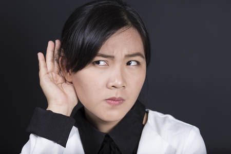 listens: Businesswoman with hand behind her ear and listens carefully