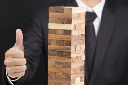 builds: Businessman Builds a Tower and Show Thumb Up