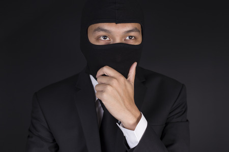 deceitful: Businessman Wearing a Balaclava Thinking Corruption Plan