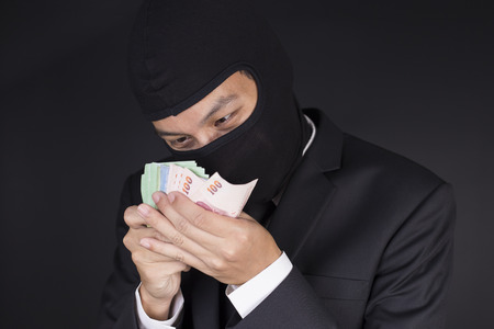 deceitful: Businessman Wearing a Balaclava Thinking Corruption Plan and Showing the Money Stock Photo