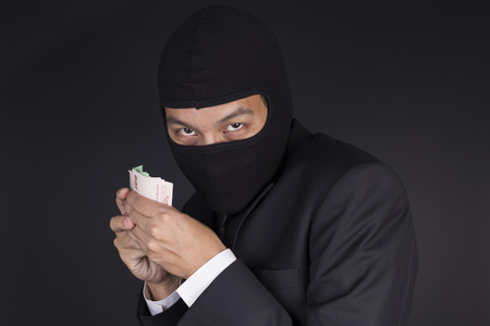 fraudulent: Businessman Wearing a Balaclava Thinking Corruption Plan and Showing the Money Stock Photo