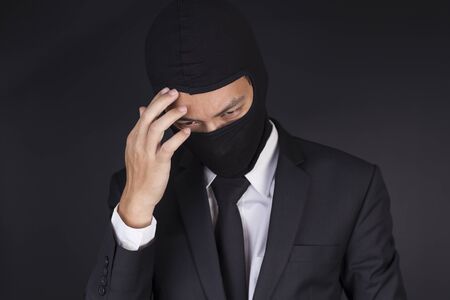 Businessman Wearing a Balaclava Thinking Corruption Plan but He Failure