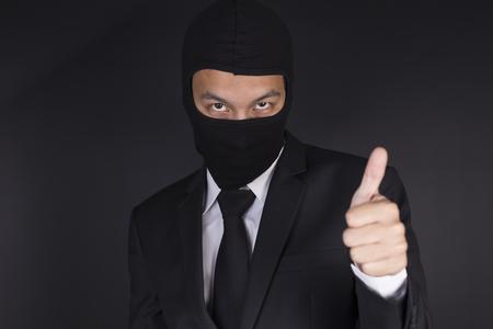 fraudulent: Businessman Wearing a Balaclava Thinking Corruption Plan and Show Thumb Up Stock Photo
