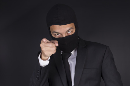 thinking of you: Businessman Wearing a Balaclava Thinking Corruption Plan and Pointing to You