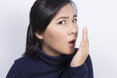Health Care: Vrouw die haar adem met haar hand Stockfoto