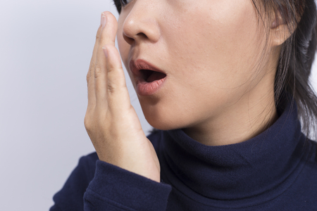 bad breath: Health Care: Woman checking her breath with her hand