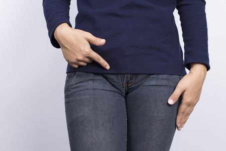 Woman with hands pointing her crotch