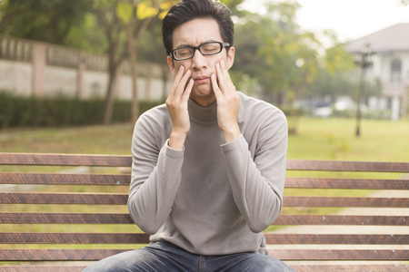 Man has tooth ache at park