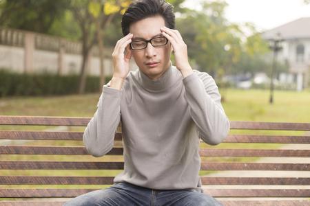 head ache: Man has head ache at park