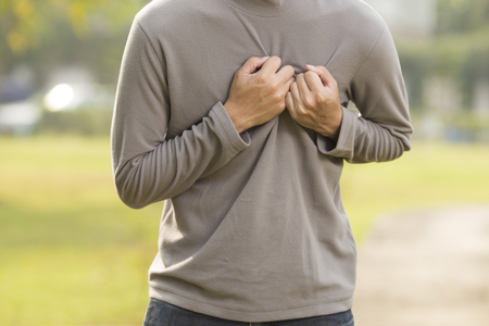 hand on chest: Man has chest pain at park Stock Photo