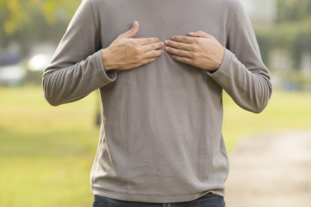 acid reflux: Man suffering from acid reflux at park