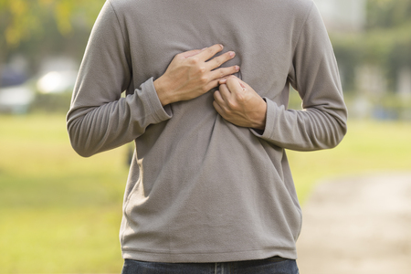 Man suffering from acid reflux at park