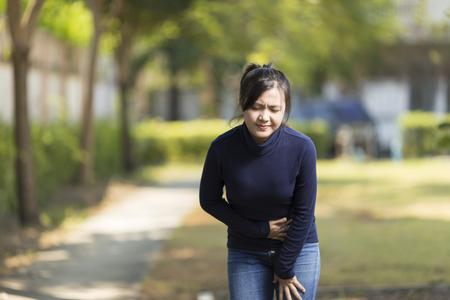女性が公園で胃の痛みを持っています。 写真素材