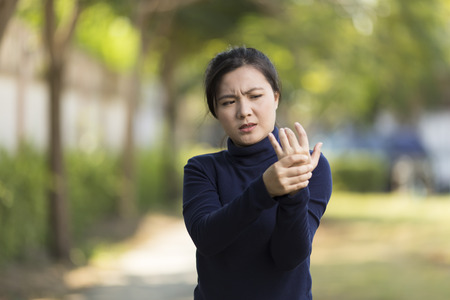 Vrouw heeft hand pijn in het park Stockfoto