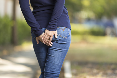 Woman has Diarrhea Holding her Butt at Park Banque d'images