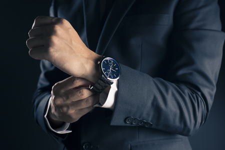 Businessman checking time from watch