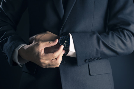 waistcoat: Businessman checking time from watch