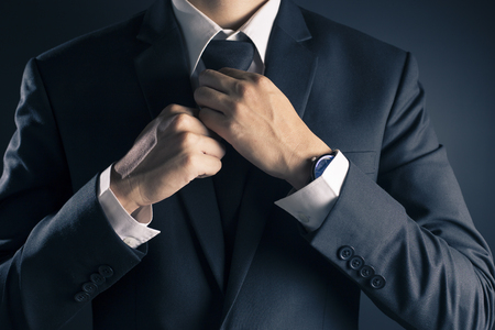 working dress: Businessman Adjust Necktie his Suit Stock Photo