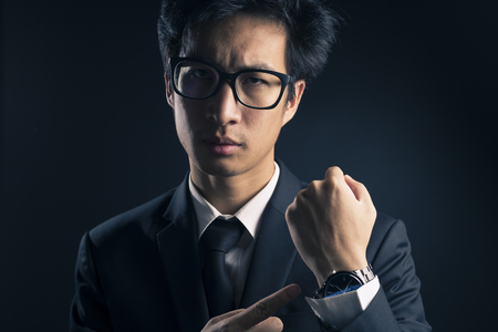 checking time: Businessman checking time from watch so serious