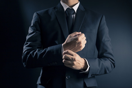 wrist cuffs: Businessman Fixing Cufflinks his Suit Stock Photo