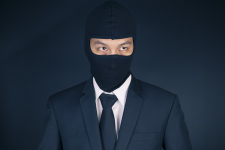 fraudulent: Businessman Wearing a Balaclava Thinking Corruption Plan