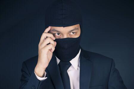 deceitful: Businessman Wearing a Balaclava Thinking Corruption Plan