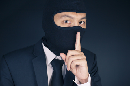 deceitful: Businessman Wearing a Balaclava Thinking Corruption Plan and Show Be Quiet Gesture