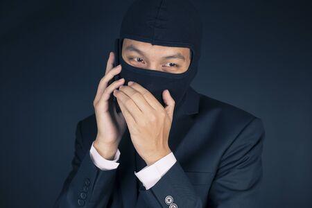 deceitful: Businessman Wearing a Balaclava Thinking Corruption Plan and Talking Smart Phone