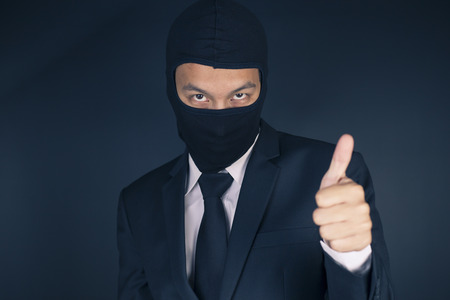 deceitful: Businessman Wearing a Balaclava Thinking Corruption Plan and Show Thumb Up Stock Photo