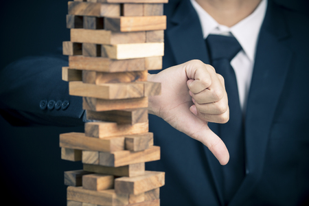 fragile economy: Businessman Builds a Tower and Show Thumb Down Stock Photo