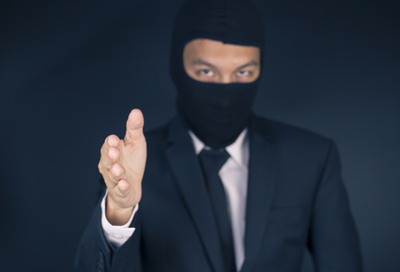 deceitful: Businessman Wearing a Balaclava Thinking Corruption Plan and Giving Hand for Shaking Hands
