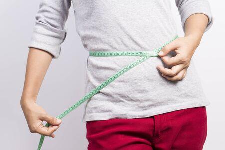 waist: Woman measuring her waist Stock Photo