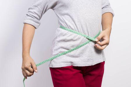 woman measuring: Woman measuring her waist Stock Photo