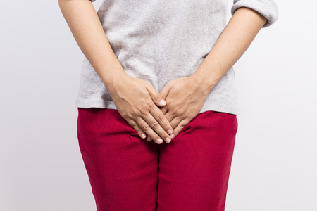 Woman with hands holding her crotch 스톡 콘텐츠