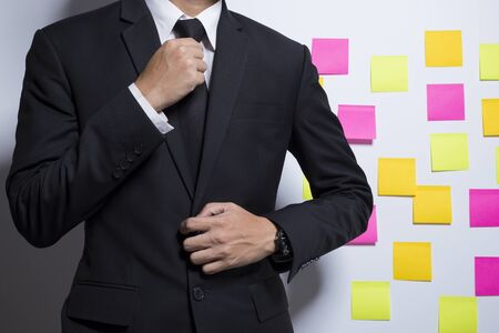 notepaper: Businessman adjusting his costume on notepaper background Stock Photo