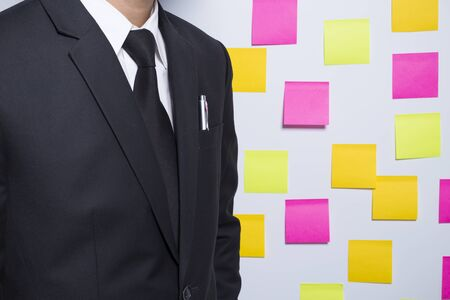 notepaper: Businessman and his pen on notepaper background