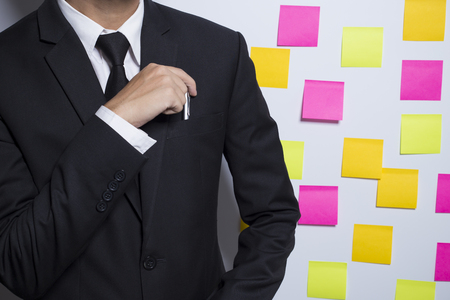 forgetful: Businessman and his pen on notepaper background