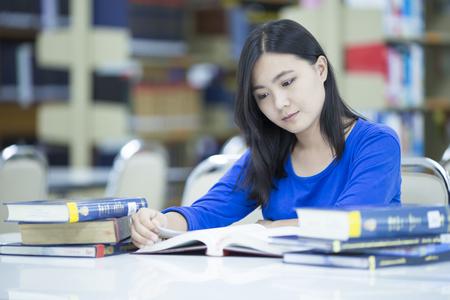 trabajando duro: Mujer que piensa algo en la biblioteca Foto de archivo