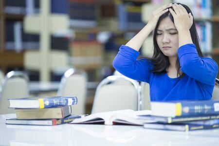 head ache: Woman has head ache in the library
