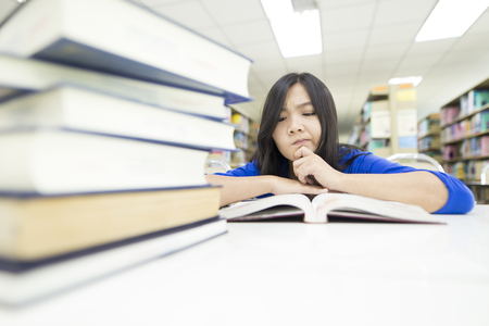 hard to find: Woman thinking something in the library Stock Photo